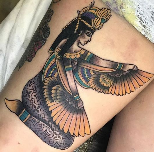 Tatuagem colorida feita na coxa com o desenho da Deusa Isís sentada segurando um tecido de penas em seus braços.