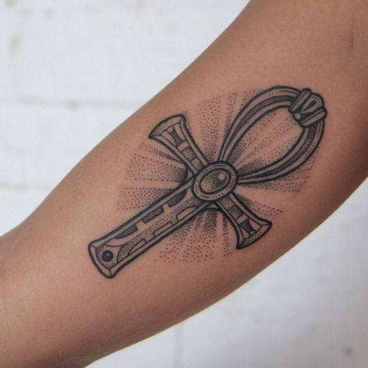 Tatuagem de uma cruz Ankh feita em tons de cinza e pequenos detalhes em pontilhismo