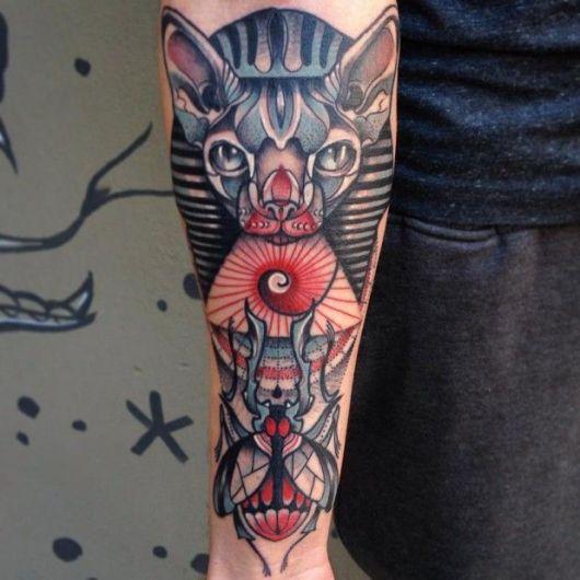 Tatuagem colorida do rosto da deusa Bastet com um escaravelho logo abaixo dela.