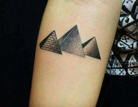 Tatuagem de três pirâmides, uma ao lado da outra. Uma tem as paredes lisas, outra tem as paredes com tijolos visíveis e a outra é formada a partir de diversos pontos conectados.