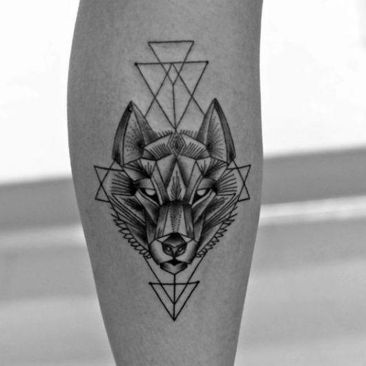 Foto de uma tatuagem feita na panturrilha da cabeça de um lobo rodeada por formas geométricas
