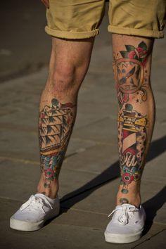 Foto das duas pernas de um homem com um navio tatuado em uma e um farol tatuado na outra.