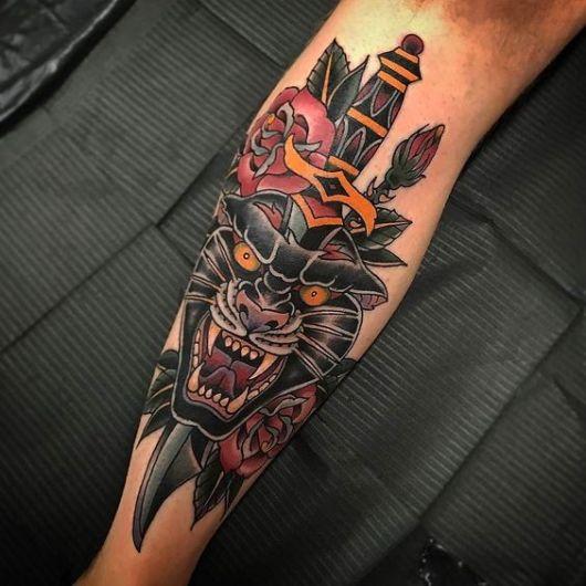 Tatuagem colorida na canela de um punhal rodeado de rosas atravessando a cabeça de uma pantera furiosa.