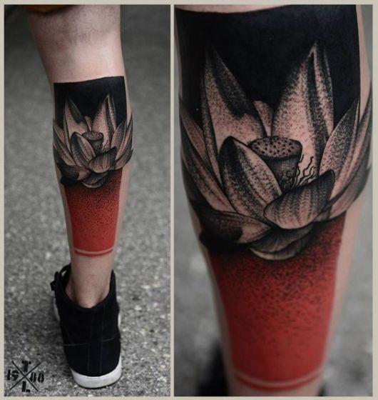 Foto de uma tatuagem na panturrilha com uma flor de lótus no centro de dos quadros: um preto e um vermelho.
