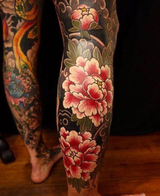 Tattoo oriental na perna de um homem com foco nas flores de cerejeira em um fundo preto.