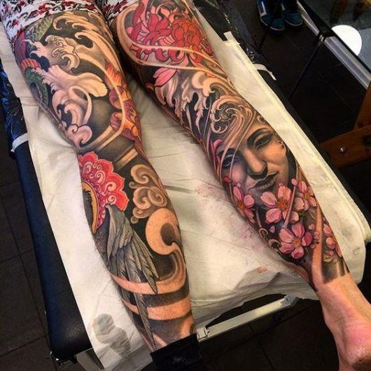 Tatuagem com diversos símbolos da cultura oriental cobrindo as duas pernas de um homem deitado.