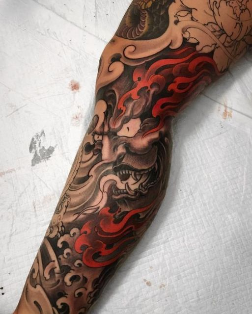 Tatuagem na perna de uma máscara hannya com expressão furiosa com chamas ao seu redor.