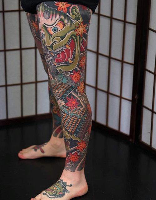 Tatuagem oriental cobrindo a perna inteira de um homem com destaque para uma máscara hannya e um samurai.