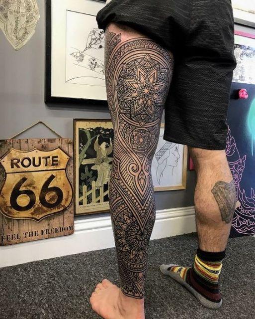 Tatuagem cobrindo a perna toda de um homem com diversas linhas e mandalas em sua composição.