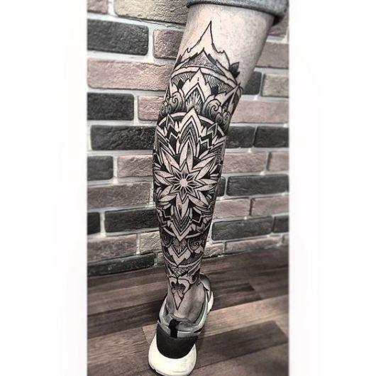 Tatuagem na panturrilha de uma mandala que se assemelha a uma flor e vai se expandindo para outras formas.