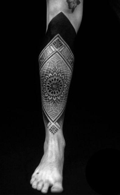 Tatuagem de uma mandala na canela rodeada por formas geométricas.
