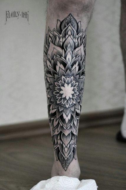 Tatuagem uma mandala na canela de um homem feita inteiramente em tons de cinza.