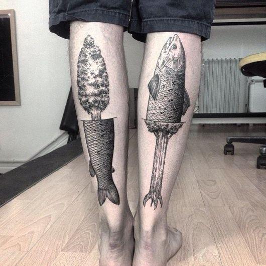 Duas tatuagens, uma em cada panturrilha. em uma há um peixe que se transforma em árvore e na outra há uma árvore que se transforma em peixe.