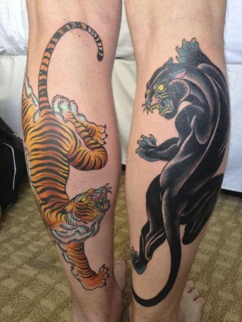 Duas tatuagens, uma em cada panturrilha. Em uma vemos um tigre e na outra uma pantera. Um olha agressivamente para o outro.