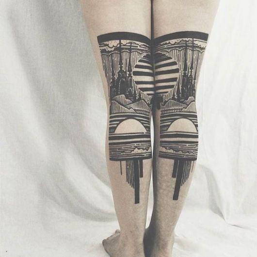 Duas tattos, uma em cada perna. Juntas, elas formam uma bela paisagem de uma floresta.