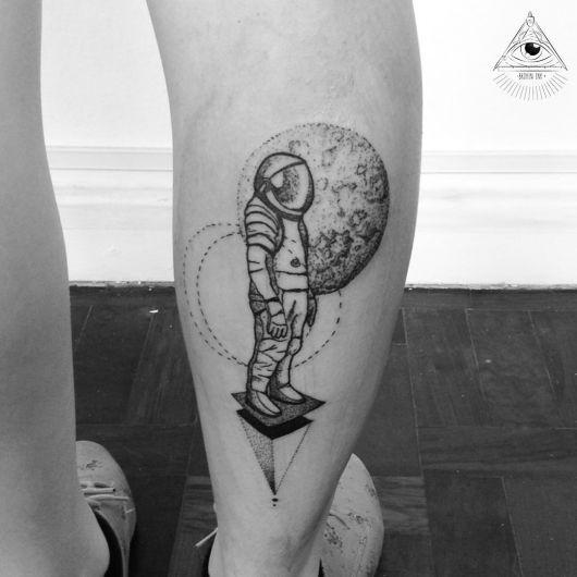 Tatuagem na panturrilha de um astronauta repousando em uma superfície plana com a lua atrás dele