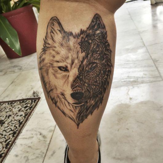 Tatuagem na panturrilha de um lobo com o rosto dividido pela metade. Uma metade é comum e a outra é repleta de detalhes que se parecem com um mosaico.
