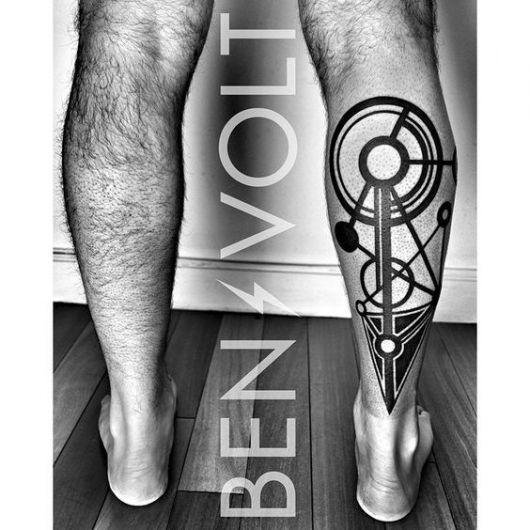 Tatuagem de formas geométricas como triângulos e círculos feita na panturrilha de um homem.