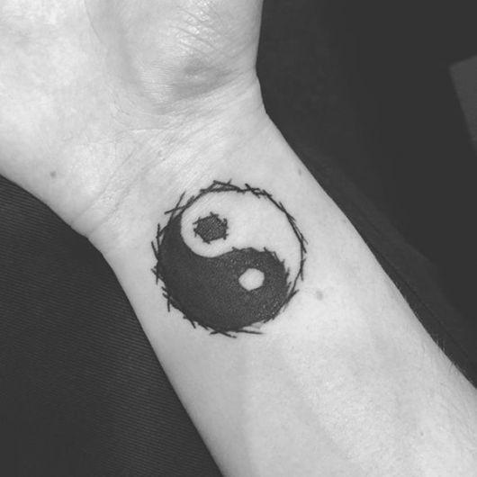 Tatuagem no pulso de um yin yang desenhado com as extremidades irregulares, de uma forma que o círculo nunca se fecha completamente.