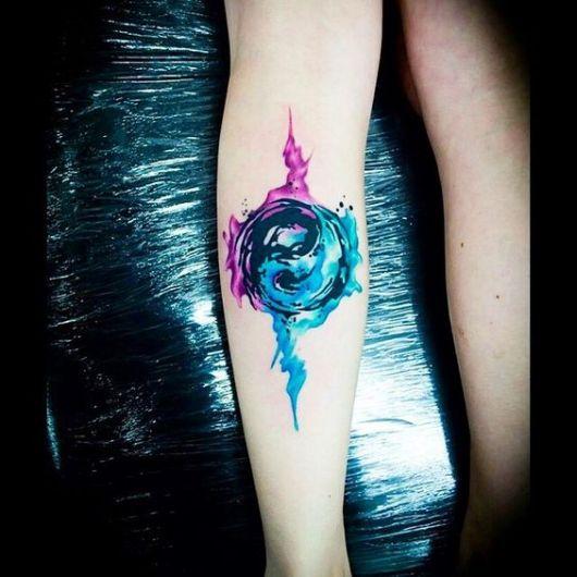 Tatuagem aquarela do Yin Yang com um lado feito de rosa e outro de azul, as cores escorrem da tattoo dando vivacidade à ela.