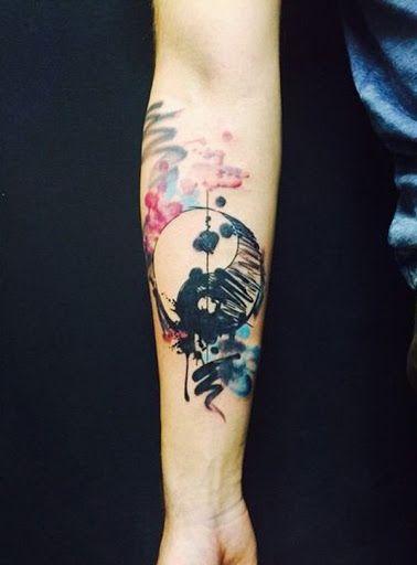 Tatuagem aquarela do Yin Yang feita com pequenos borrões que dão a impressão de que a tattoo é um esboço.