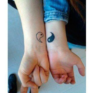 Dois pulsos de pessoas diferentes. Em cada um deles há um metade do Yin Yang.