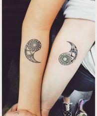Dois braços de pessoas diferentes. Em cada um há uma metade do Yin Yang estilizada.