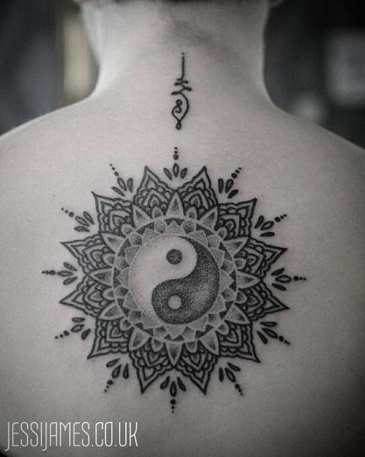 Tatuagem nas costas de um Yin Yang rodeado por uma mandala toda feita em tons de cinza.