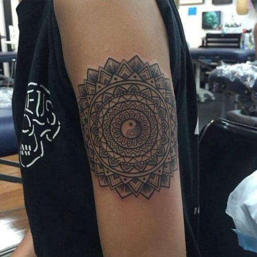 Tatuagem em tons de cinza com uma mandala grande feita no braço e um Yin Yang no centro dela.