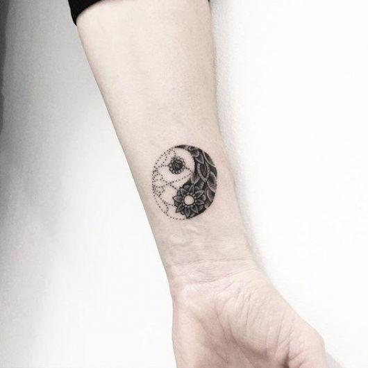 Tatuagem de Yin Yang no pulso com pequenas pétalas desenhadas em seu interior.
