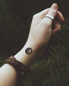 Tatuagem pequena na lateral do pulso com o desenho de um Yin Yang simples pequeno.