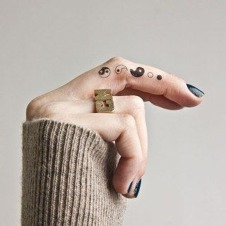 Tatuagem pequena na lateral do dedo das diferentes partes que formam o Yin yang.