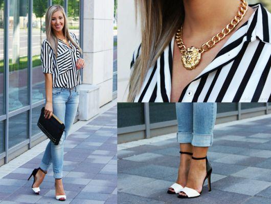 Modelo usa calça jeans azul, blusa branca com listras pretas e sandalia preta e branca.