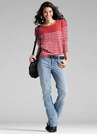 Modelo usa calça jeans flare com cinto preto e blusa vermelha com listras brancas.