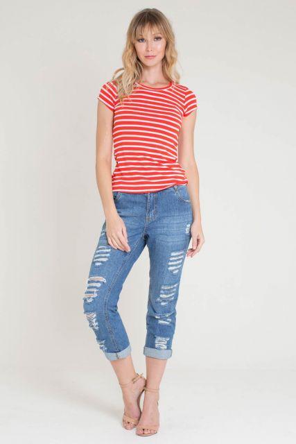 Modelo usa calça boyfriend, sandália vermelha e blusa vermelha com listras brancas.