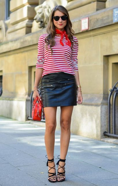 Modelo usa saia preta de couro, blusa vermelha ccom listras brancas e sandalia preta de amarrações.