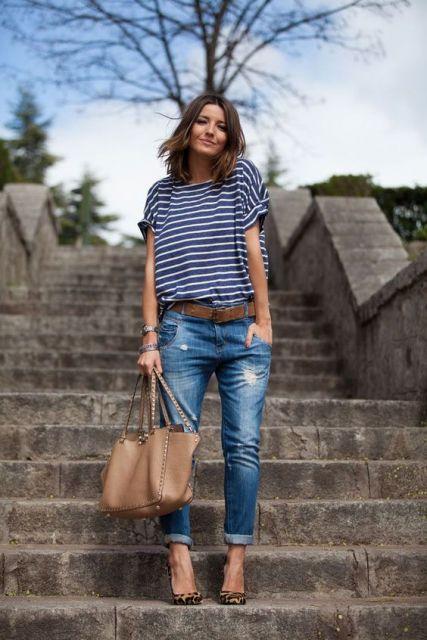 Modelo usa calça jeans azul, blusa listrada azul com branco e sandalia.