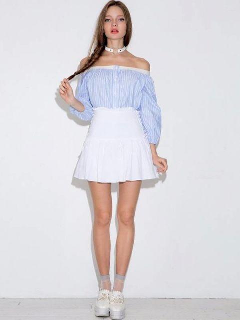Modelo veste blusa ombro a ombro azul com listras brancas, saia e sapato branco.