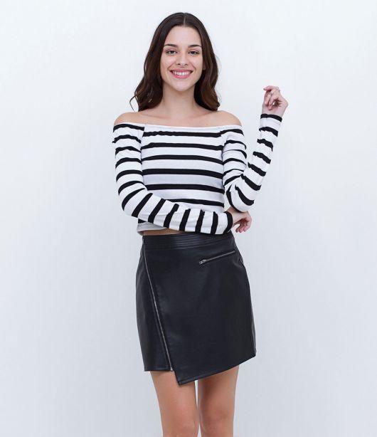 Modelo usa blusa listrada preta e branca e saia preta.
