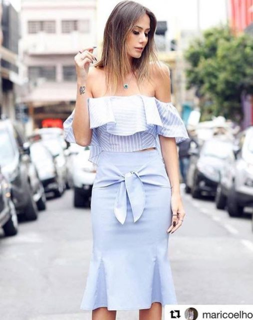 Modelo usa saia azul claro, blusa ombro a ombro listrada em branco e azul com babados.