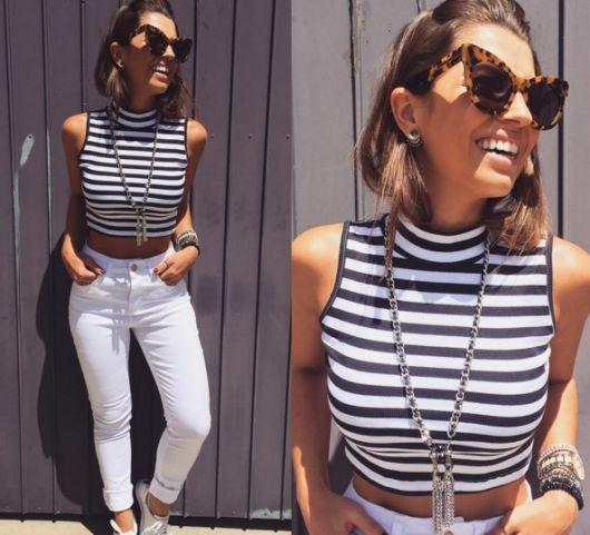 Modelo usa calça jeans branca, blusa regata cropped listrada nas cores preto e branco com tenis.