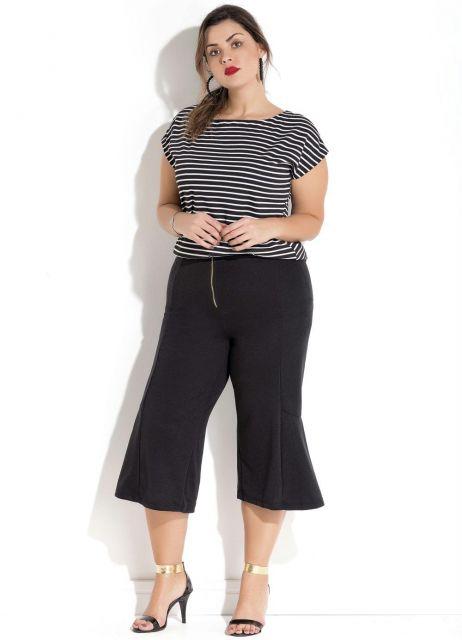 Modelo veste calça preta pantacourt com blusa listrada preta e branca.