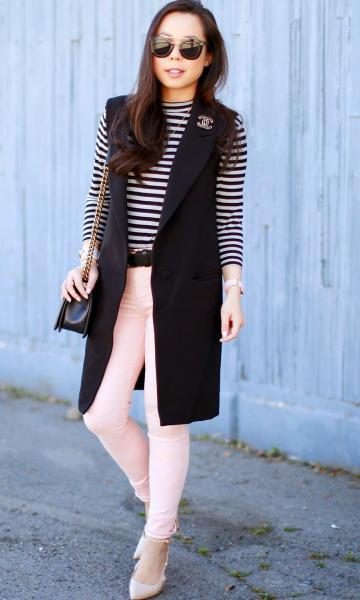 Modelo usa calça jeans rosê, sapato nude, blusa listrada preto e branco com maxi colete preto.