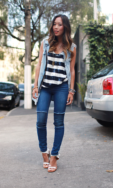 Modelo usa calça jeans azul, blusa listrada em preto e branco colete jeans e sandalia branca.