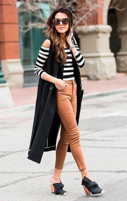 Modelo usa sapato preto, colete longo preto e blusa listrada na cor branco e preto e calça caramelo jeans.