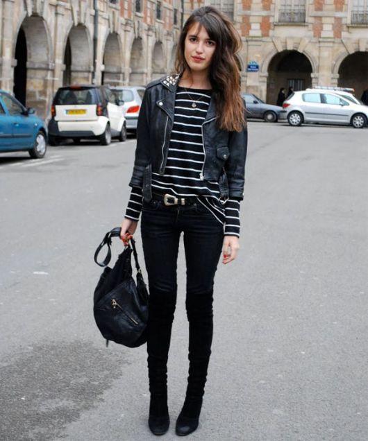 Modelo usa jaqueta de couro preta, calça preta, blusa listrada de preto e branco e bota preta.