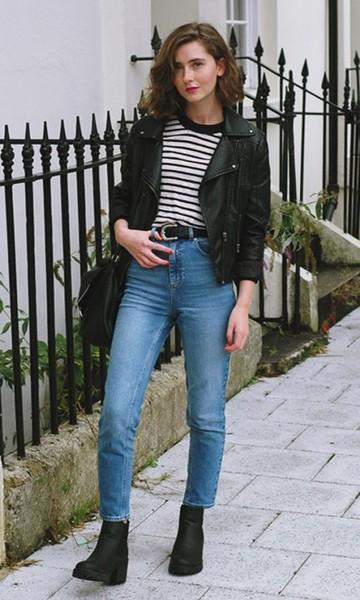 Modelo usa calça azul jeans, blusa branca listrada de preto, jaqueta de couro preta bolsa e bota na mesma cor.