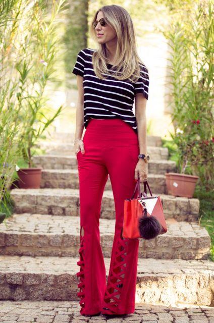Modelo usa calça vermelha flare, blusa preta com listras brancas e bolsa vermelha.