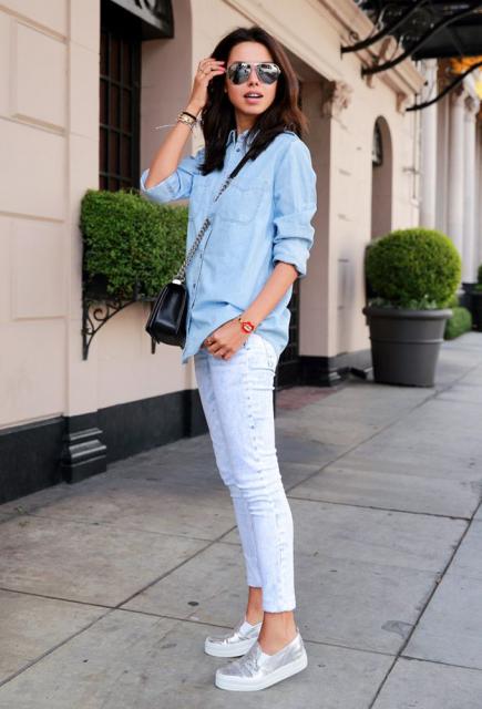 Modelo usa sapatilha branca com cinza, calça branca e camisa jeans azul clara.