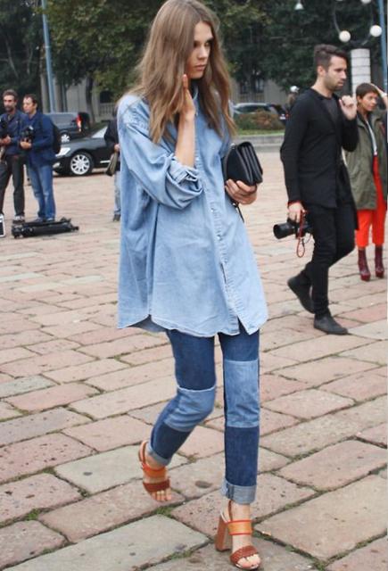 Modelo usa calça jeans com remendos em diversos tons de azul, sandalia caramelo e camisa azul clara.